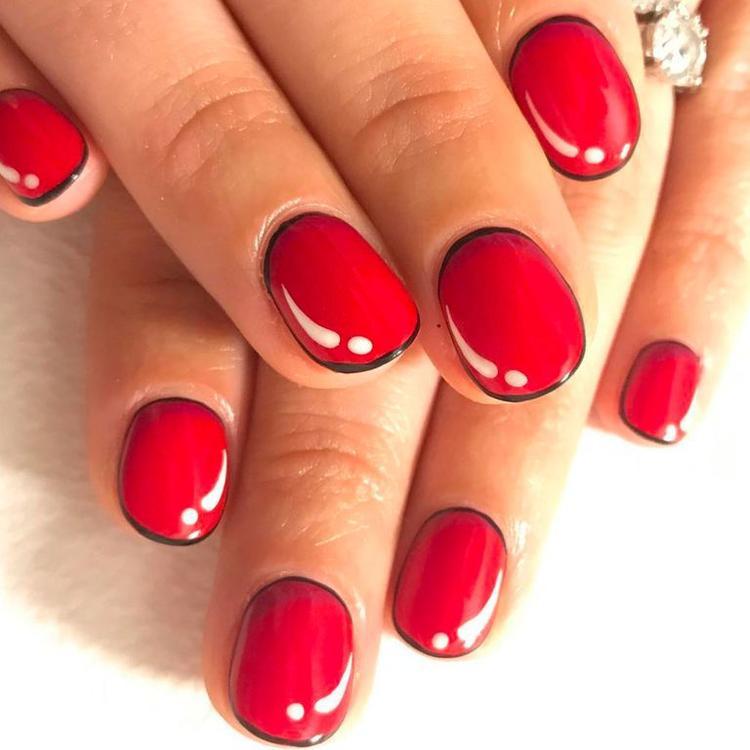 Kiểu kẻ viền móng màu đen, sau đó phủ 1 lớp sơn đỏ và tạo điểm nhấn bằng những dấu chấm thang cũng góp phần đem đến hiệu ứng nổi bật.