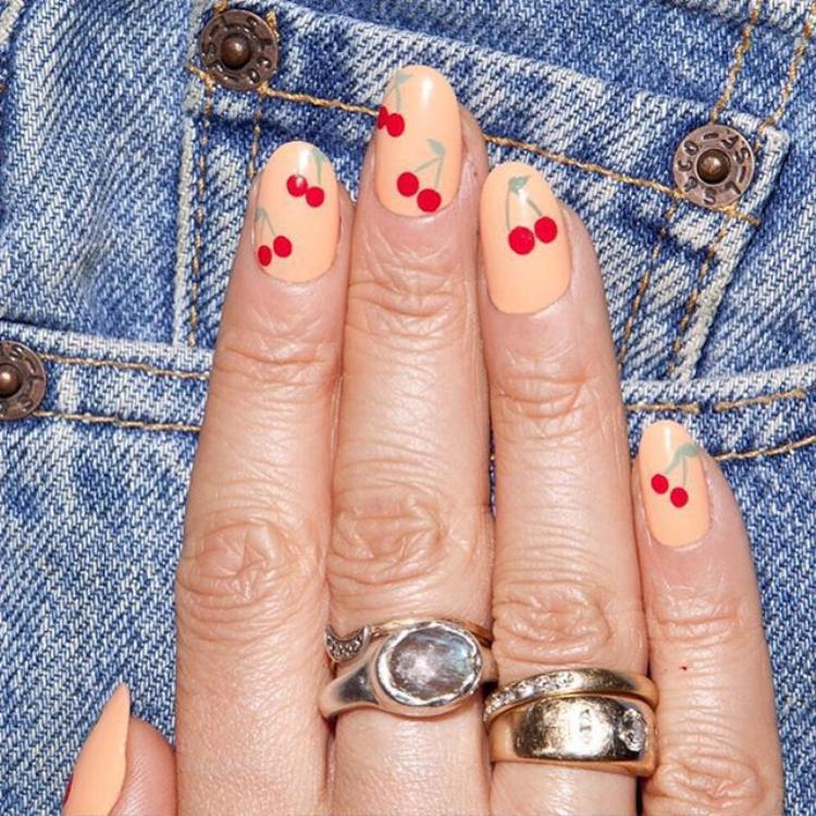 """Một bộ nail với điểm nhấn là những trái cherry đỏ rực, thích hợp với những bạn gái yêu thích phong cách nữ tính. Nếu quyết định chọn 1 bộ móng theo phong cách này, """"hội, chị em"""" hãy nhớ vẽ những điểm nhấn nhỏ, có kích thước vừa phải, tránh trường hợp bộ móng trở nên lòe loẹt, quê kiểng."""