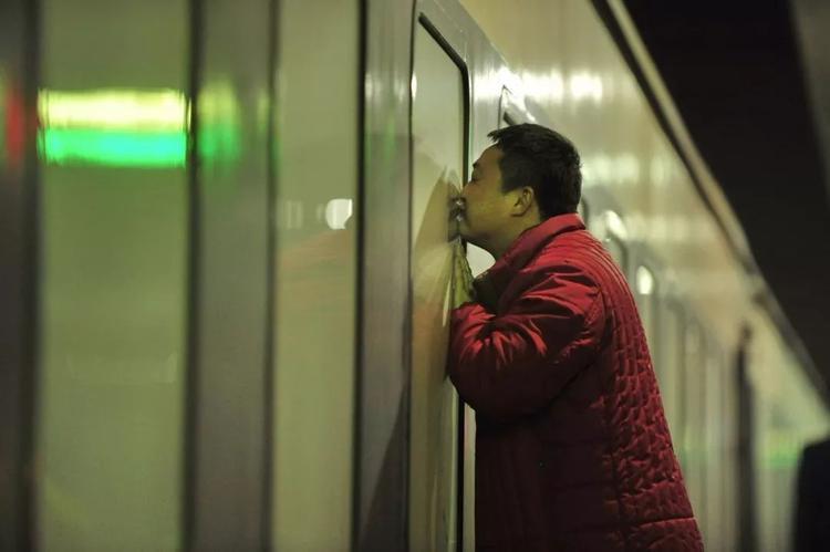 Cha hôn tạm biệt con trai qua lớp cửa kính tàu hỏa.