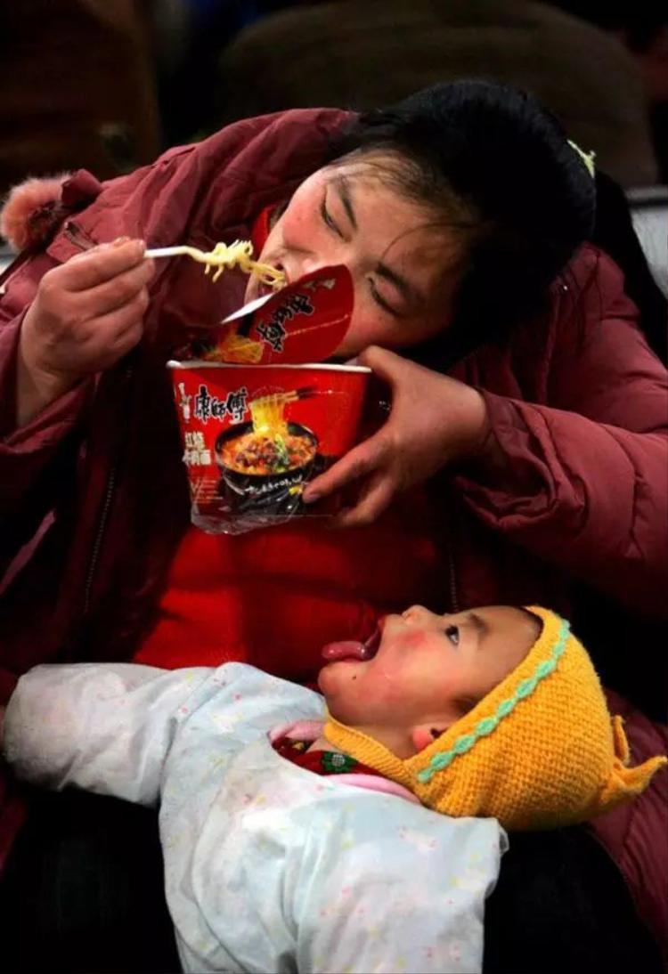 Hai mẹ con tranh thủ ăn vội bát mì gói trong lúc chờ tàu tới. Ảnh chụp vào năm 2006.