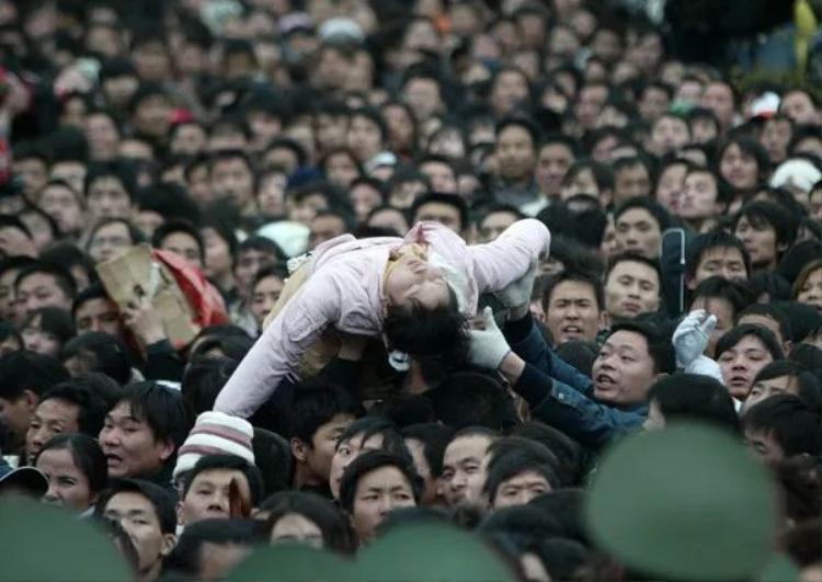 """Mọi người đang cố gắng đưa một hành khách bị ngất ra khỏi đám đông. Ảnh chụp trong đợt """"di cư lớn nhất hành tinh"""" năm 2008 tại Quảng Châu."""