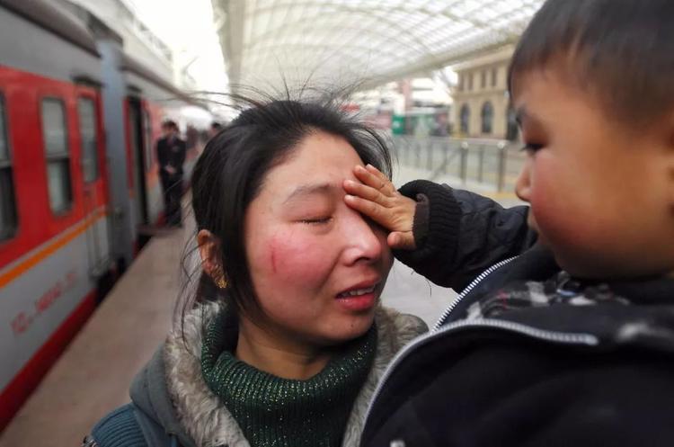 Một đứa trẻ lau nước mắt cho mẹ tại trạm xe lửa Thanh Đảo năm 2008.