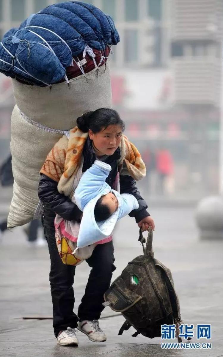 Người mẹ đang còng lưng mang đống hành lý quá khổ trên lưng cùng đứa con nhỏ vội vàng đi tới nhà ga Nam Xương để kịp chuyến tàu.
