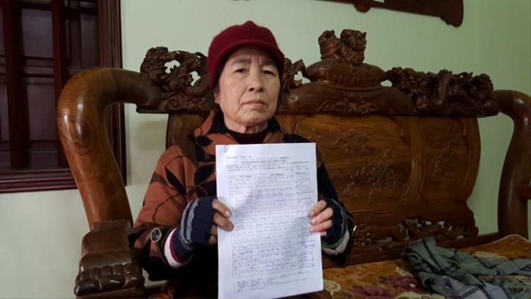 Bà ngoại bé Nhật Linh với tờ giấy có chữ ký của mọi người. (Ảnh: Thanh Niên)