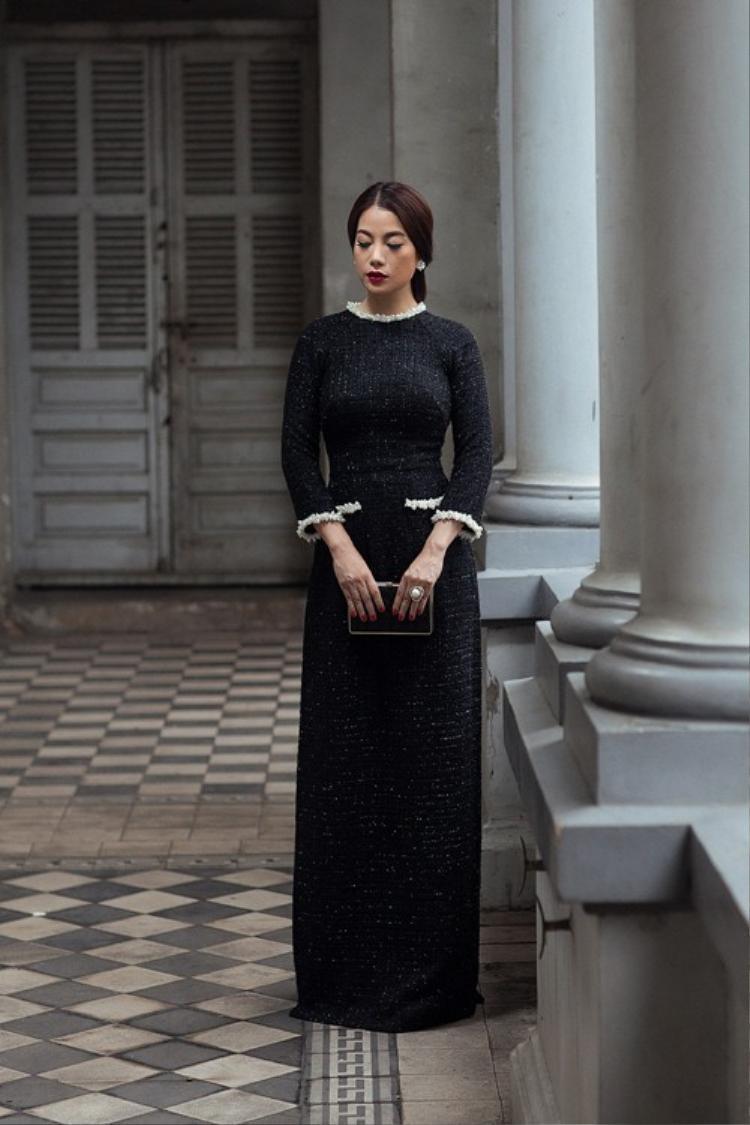 Trương Ngọc Ánh Chất lại diện một bộ áo dài đen cách điệu, được may bằng chất liệu vải tweed dày dặn. Kiểu áo dài này rất hợp để các cô gái diện vào mùa đông lạnh giá.
