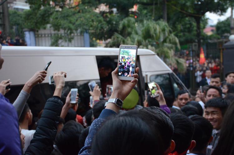 Ai ai cũng háo hức giơ máy điện thoại chụp hình khi xe ô tô đến đón các cầu thủ.