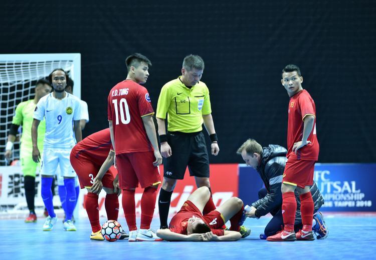 Một cầu thủ Việt Nam phải nằm sân sau tình huống đánh nguội của cầu thủ Malaysia.