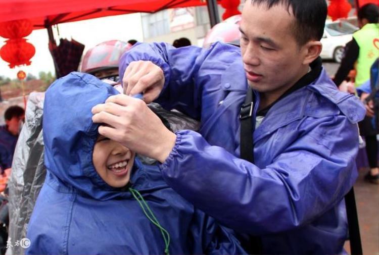 Một người bố giúp con chỉnh lại áo mưa để về quê.