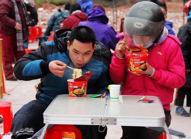 Một cặp vợ chồng ăn vội cốc mì tôm hộp để lót bụng.