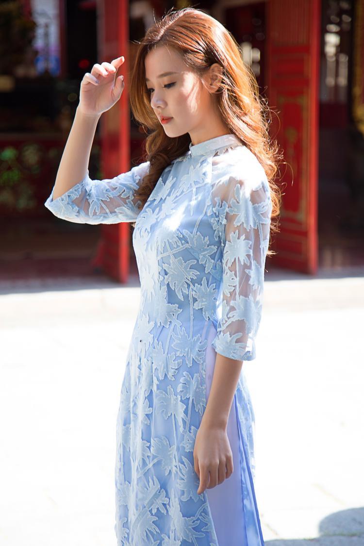 Chất liệu voan lưới quen thuộc trong những thiết kế áo dài xưa được tạo điểm nhấn khi phối cùng chi tiết ren ấn tượng giúp hình ảnh cựu hot girl trở nên mới mẻ, khác với những bộ ảnh áo dài trước đây.