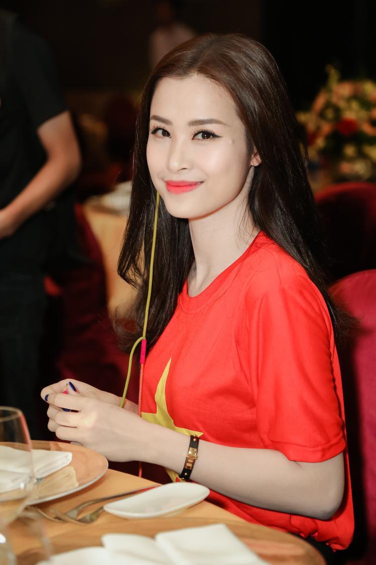 Đông Nhi xuất hiện xinh đẹp và giản dị trong chiếc áo thun đỏ in hình sao vàng, cùng quần đen đơn giản