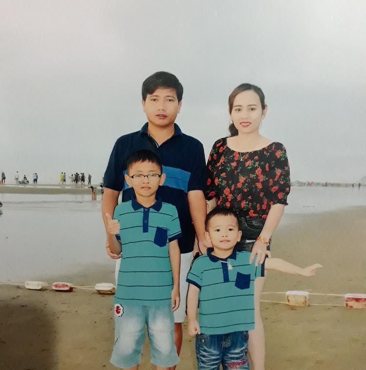 Phan Đức Thắng (cậu bé đeo mắt kính, áo xanh) chụp ảnh cùng bố mẹ và em trai.