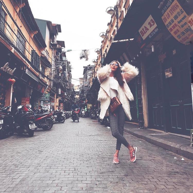 """Lan Khuê lại chưng diện cả cây áo khoác lông to sụ khi xuống phố tuần qua. Để không khiến phần nhìn bị """"làm quá"""", người đẹp lựa chọn mix theo dạng layer với áo phông ôm và quần legging. Chiếc kính mát trong cùng giày thể thao màu hồng là 2 món phụ kiện đắt giá được HLV The Look sử dụng khiến outfit trẻ trung hơn rất nhiều."""