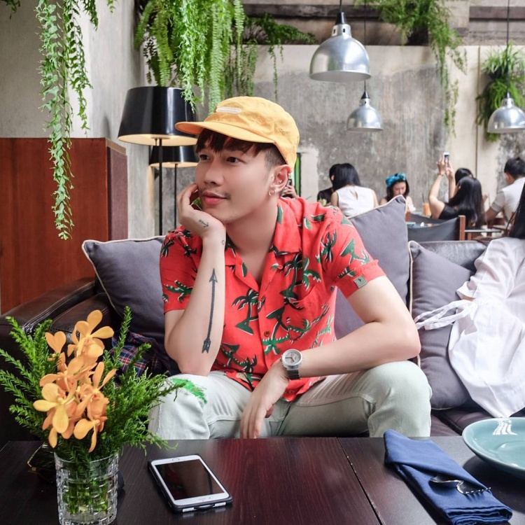 Stylist Lê Minh Ngọc khá trẻ trung với áo sơ-mi họa tiết nhiệt đới có tông màu cam bắt mắt, anh lựa chọn phối cùng mũ cam để tạo nên tổng thể phù hợp.