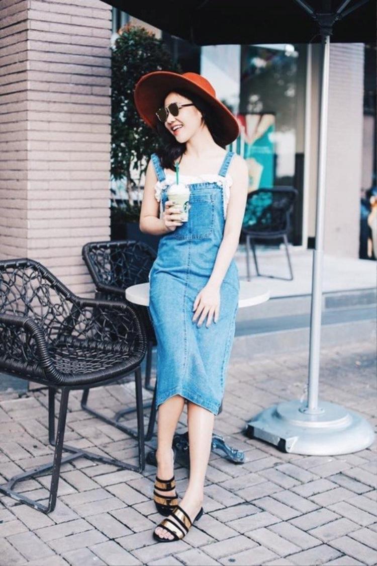 Chiếc váy yếm jeans được mix match hoàn hảo với chiếc nón vành rộng và mắt kính kiểu độc đáo.