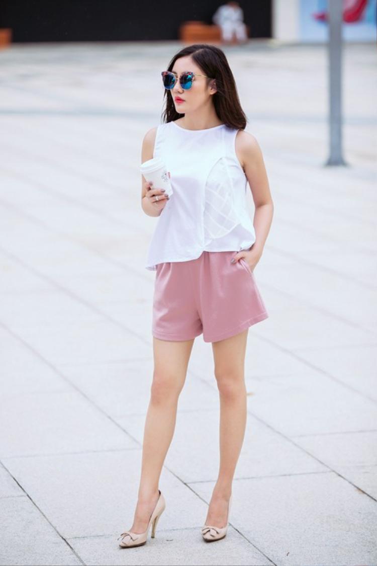 Chọn phong cách đơn giản với quần short màu pastel và áo trắng sát nách mát mẻ cũng đủ làm cô nổi bật hết phần người khác. Khi cần nữ tính dịu dàng thì một chiếc váy hồng như thế này là đủ với cô.