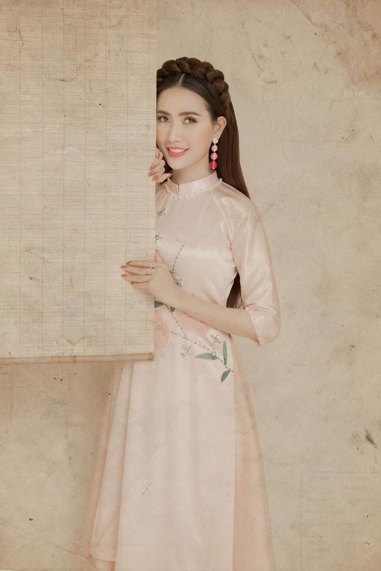 Với tà áo dài hồng phấn nhẹ nhàng, người đẹp thay đổi kiểu tóc sang cách tết bím, để xõa dài nữ tính.