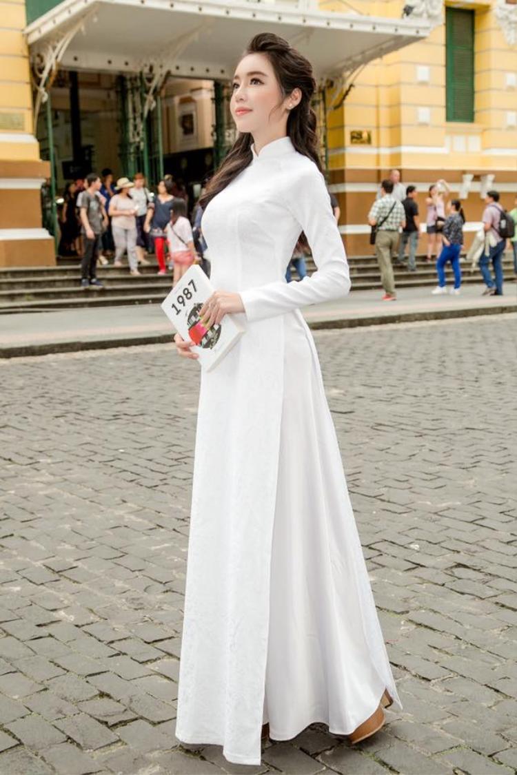 """""""Bà mẹ hai con"""" Elly Trần khiến nhiều người phải bất ngờ với thân hình đồng hồ cát trong tà áo dài trắng. Thường xuyên ăn mặc táo bạo, song trong tà áo dài người đẹp vẫn giữ được vẻ e ấp, thanh lịch."""
