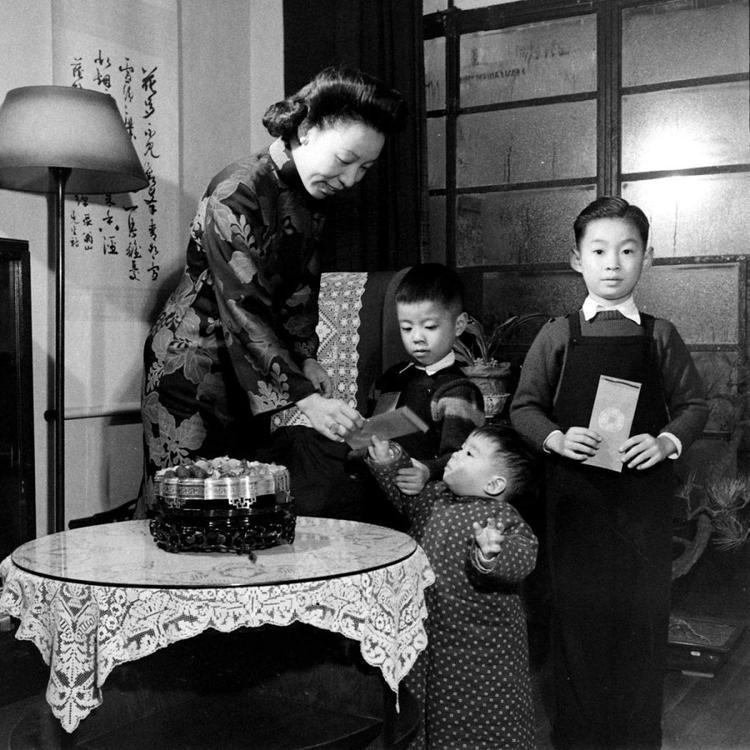 Bà mẹ mặc trang phục truyền thống, lì xì cho các con trong dịp Tết.