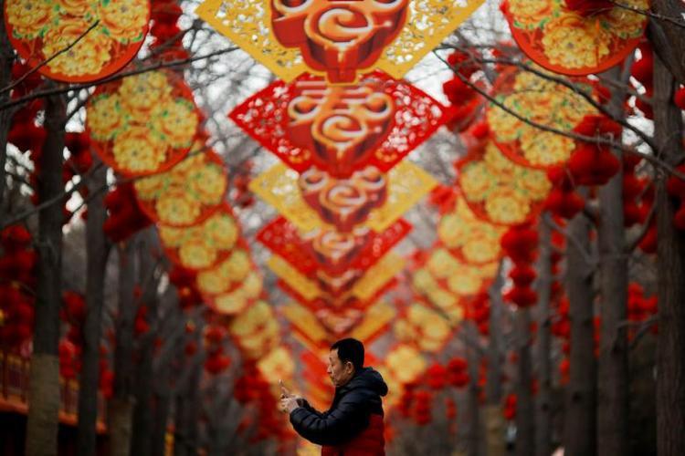 Chỉ vài giờ nữa, châu Á sẽ bước sang năm mới âm lịch Mậu Tuất 2018, nhưng từ nhiều tuần thậm chí vài tháng trước, không khí Tết Nguyên đán đã rộn ràng khắp nơi. Trong ảnh, hai hàng cây được treo đèn lồng đỏ trước thềm năm mới tại một công viên ở thủ đô Bắc Kinh, Trung Quốc.