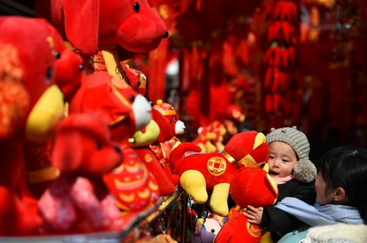 Một đứa trẻ ở tỉnh An Huy, Trung Quốc đang ôm những đồ vật trang trí trong dịp Tết cổ truyền.