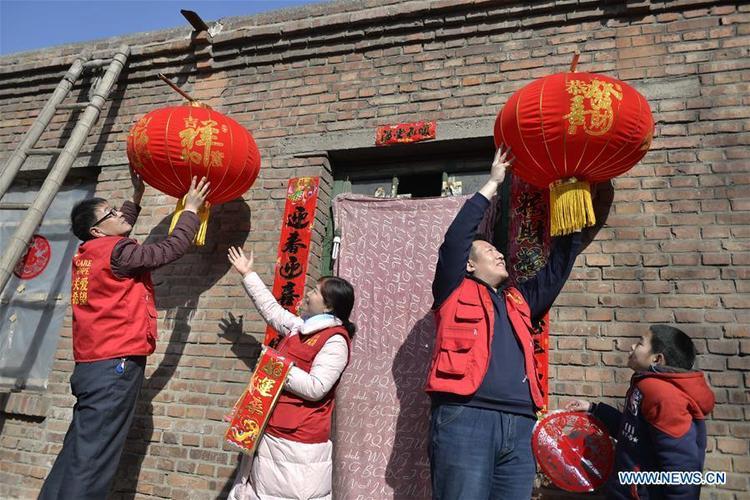 Những tình nguyện viên đang giúp các gia đình nghèo khó ở Kiều Tây, Thạch Gia Trang, Hà Bắc dán câu đối và treo đèn lồng đỏ để đón năm mới.