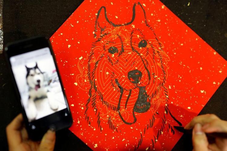 Một người phụ nữ đang vẽ hình một chú chó, linh vật năm Mậu Tuất, lên nền giấy đỏ ở Đài Bắc, Đài Loan.