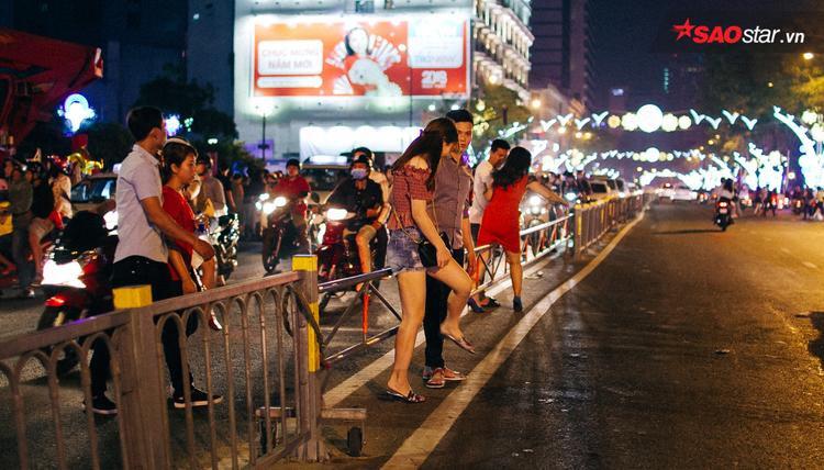 Nhiều người băng qua dải phân cách để sang đường.