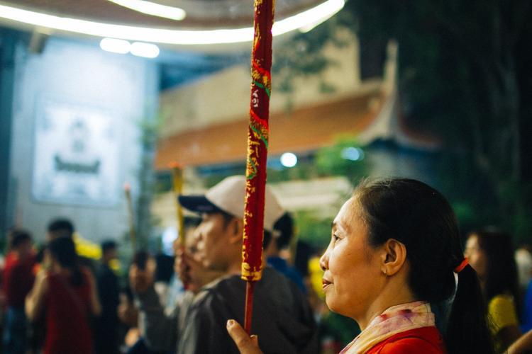Một người phụ nữ đã đốt cây nến thuê rồng trước tượng Quan âm.