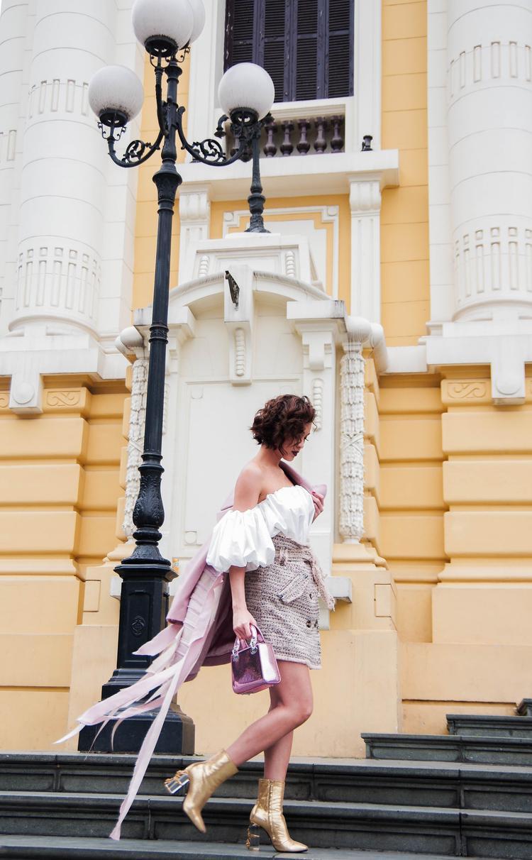 Siêu mẫu gốc Hà Nội hoàn thiện trang phục với boots ánh kim sắc vàng đế trong cùng chiếc túi hàng hiệu màu hồng xuyệt tông với áo khoác ngoài.