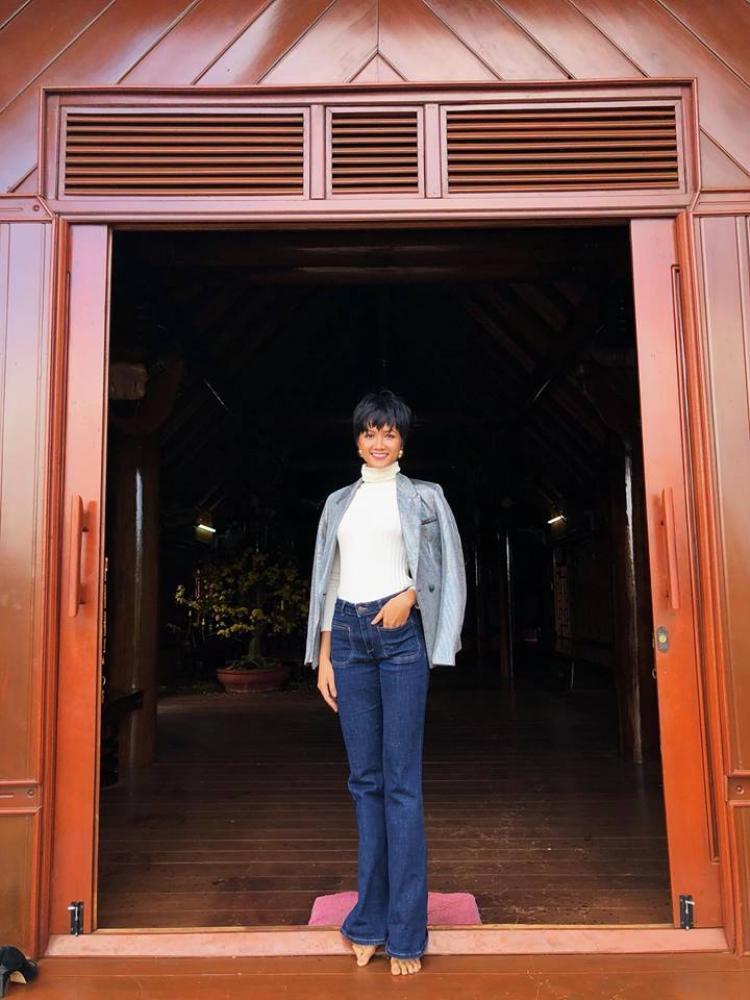 Hoa hậu Hoàn vũ Việt Nam 2017 H'Hen Niê chọn phong cách đơn giản với áo len cùng quần jeans ống loe khoe đôi chân dài miên man. Vì thời tiết lạnh nên hoa hậu khoác thêm áo ngoài để giữ ấm và hoàn thiện set trang phục.