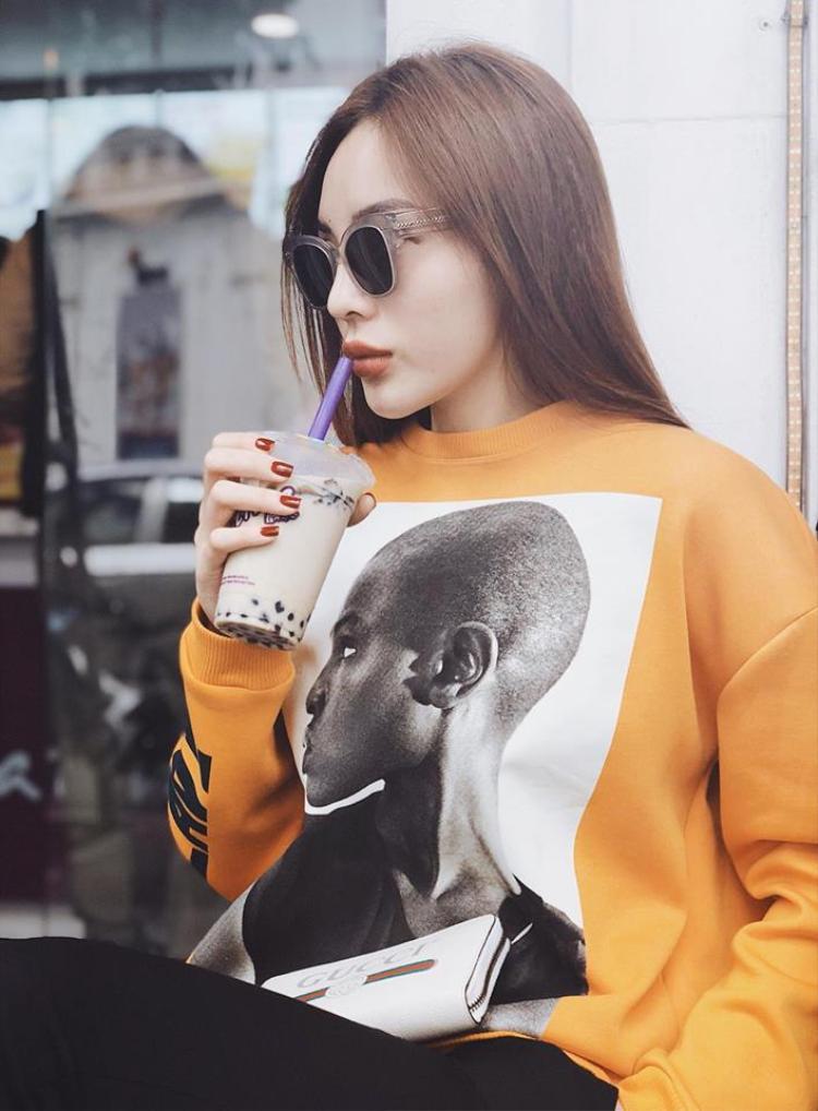 Chiếc áo phông tay dài màu vàng được Hoa hậu Việt Nam 2014 chọn mặc vào mùng 2 Tết phối cùng quần đen. Bên cạnh đó, Kỳ Duyên nhấn nhá bằng chiếc kính mát và ví cầm tay Gucci sang chảnh đi kèm.