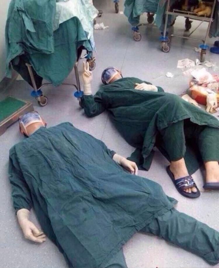 2 bác sĩ nghỉ ngơi sau khi loại bỏ thành công khối u não trong một cuộc phẫu thuật kéo dài 32 giờ.