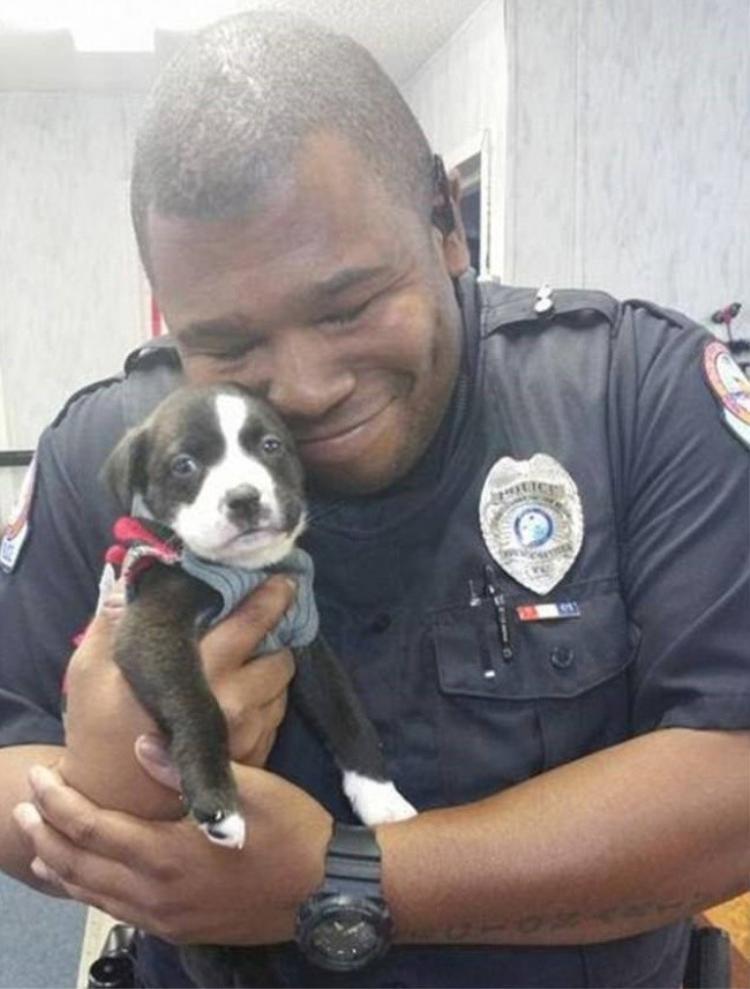 Nhân viên cảnh sát âu yếm chú chó mới được nhận nuôi.