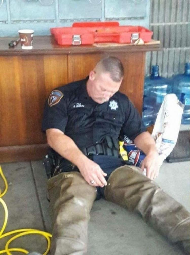 Nhân viên cảnh sát Mỹ nghỉ ngơi sau nhiều giờ giúp vô số người dân gặp nạn doảnh hưởng của bão Harvey,