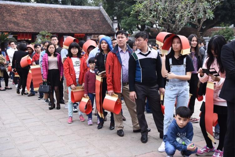 Trong sân Văn Miếu, rất đông người xếp hàng chờ xin chữ từ các ông đồ. Ảnh: VnExpress.