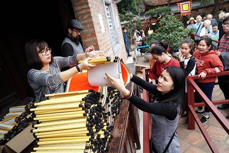 Ở khu vực nhà Thái học, giấy được bán tại một quầy riêng. Người dân mua giấy với giá 100.000 đồng rồi đi xin chữ. Ảnh: Thanh niên.