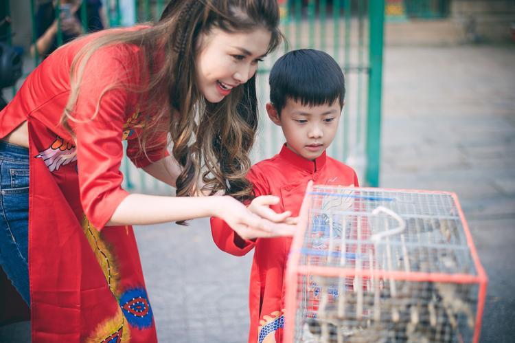 Đăng Anh thích thú được mẹ hướng dẫn thả chim phóng sinh.