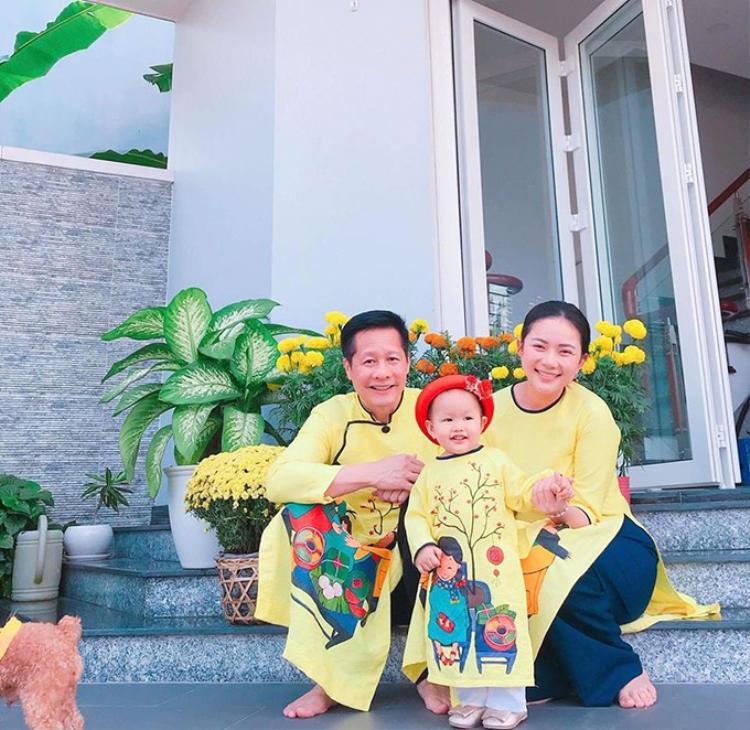"""Gia đình ba thành viên của Phan Như Thảo diện đồng phục áo dài vàng đi du xuân. Bà mẹ một con chia sẻ: """"Một năm sum vầy đầm ấm. Gia đình là tất cả""""."""