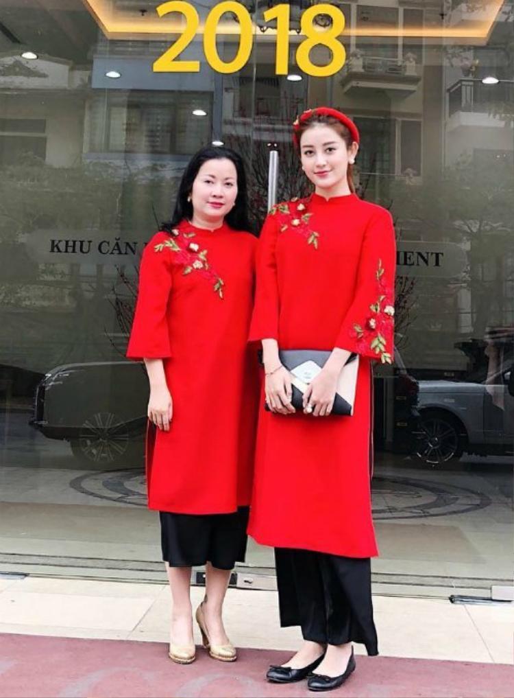Áo dài là một trong những trang phục được nhiều người ưa chuộng vào mỗi dịp Tết đến, Xuân sang. Huyền My cùng mẹ lựa chọn tà áo dài đỏ rực thêu họa tiết nhánh hoa trên vai và tay áo, đem đến sự nổi bật cho người mặc.