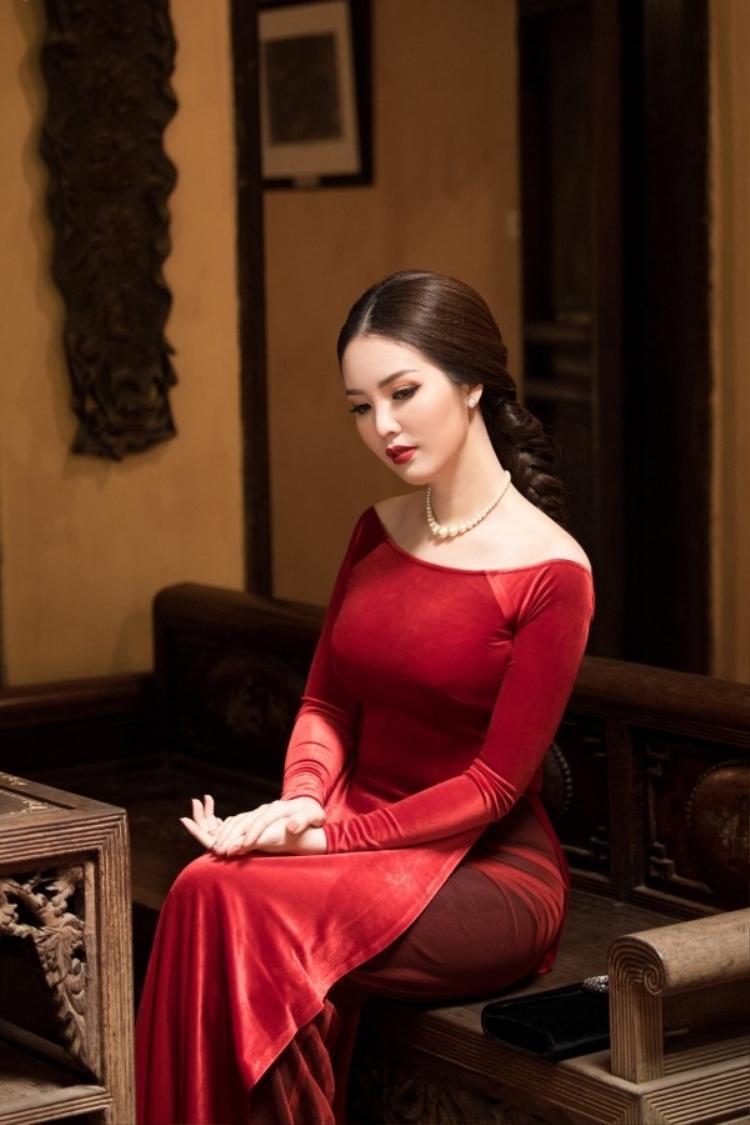 Áo dài cổ thuyền chưa bao giờ thôi quyến rũ phái đẹp, á hậu Thụy Vân chọn chiếc áo dài cổ thuyền màu đỏ sẫm để chào xuân Mậu Tuất. Chất liệu nhung càng tôn lên vẻ mặn mà, sắc sảo của á hậu.