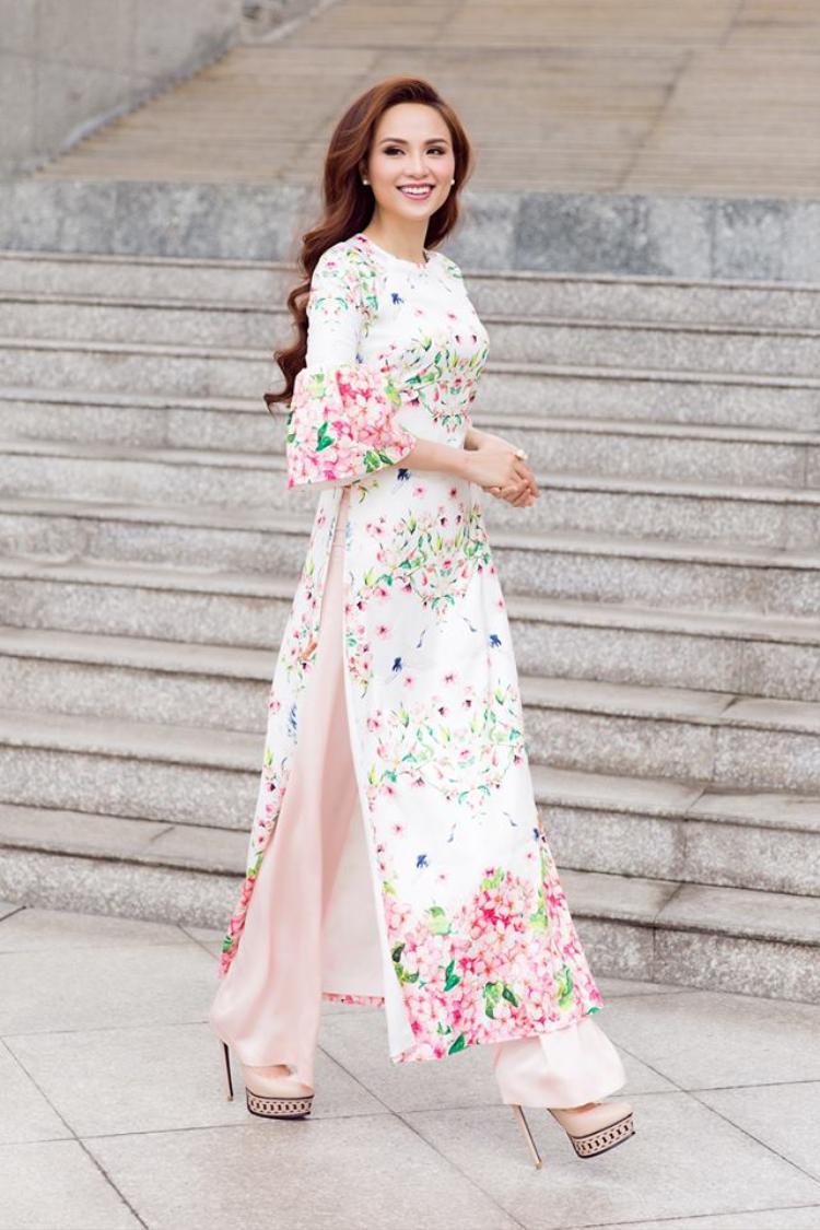 Tết này hoa hậu chọn cho mình chiếc áo dài hoa cách điệu không cổ với phần tay áo xòe bồng tạo sự trẻ trung. Mái tóc dài được uốn gợn sóng xõa tự nhiên càng góp phần làm tăng vẻ đẹp của hoa hậu gốc Sài thành.