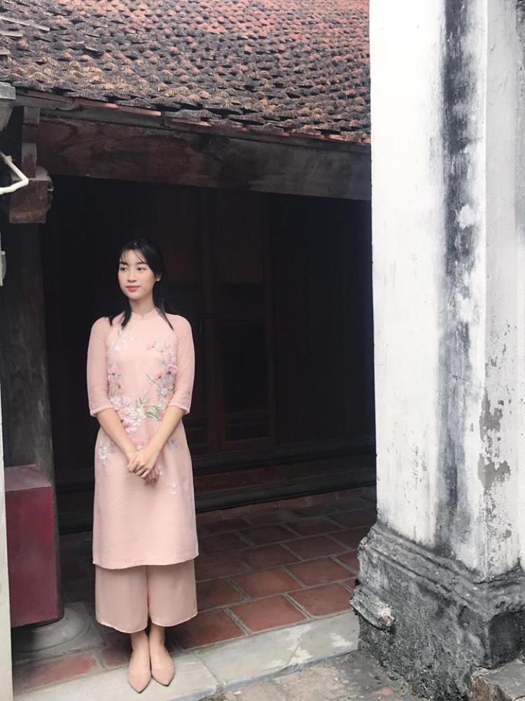 """Được ví như """"cô Tấm"""" trong số các hoa hậu của Việt Nam, dịp Tết Mậu Tuất, Đỗ Mỹ Linh chọn cho mình tà áo dài màu nude với hoa thêu nhấn nhá xinh xắn. Không làm tóc cầu kì, hoa hậu để tóc thẳng tự nhiên và hoàn thiện set trang phục bằng giày búp bê trơn đơn giản nhưng vẫn làm xao xuyến bao trái tin người hâm mộ."""