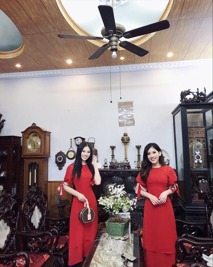 Hoa hậu Jolie Nguyễn (trái) chọn tà áo dài màu đỏ rực trong dịp Tết này. Phối cùng với đó là chiếc túi cầm tay dạng hộp sành điệu.