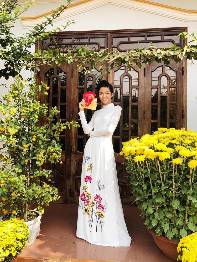Về quê nhà đón Tết Nguyên Đán, Hoa hậu Hoàn vũ Việt Nam 2017 H'Hen Niê chọn áo dài trắng truyền thống với kiểu dáng đơn giản nhưng vẫn nổi bật với hoạ tiết hoa sen được thêu tinh xảo ở phần đuôi áo. Có thể thấy, trong chiếc áo dài này hoa hậu vẫn khoe khéo được hình thể mà không cần váy áo cầu kì hay hở hang.