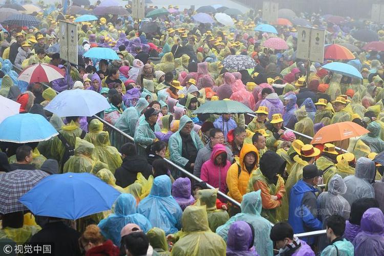 Người dân mặc áo mưa, che ô, xếp hàng dưới mưa để mua vé vào tham quan.