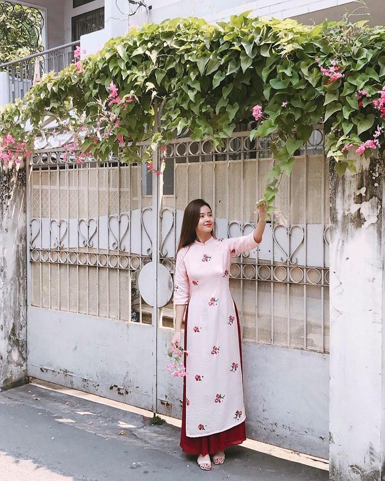 Midu xuống phố với bộ áo dài tông hồng nhẹ nhàng. Như thường lệ, cô trang điểm và để tóc suông dài tự nhiên.