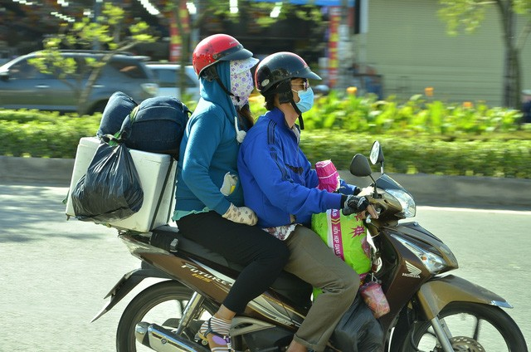 Hai vợ chồng di chuyển bằng xe máy cá nhân cùng nhiều đồ đạc.