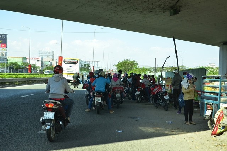 Dọc hai bên đường, những người đi xe máy tấp vào lề để nghỉ ngơi, lấy lại sức sau đoạn đường dài di chuyển trong thời tiết nắng nóng.