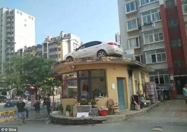 Chiếc xe của người phụ nữ bị cẩu lên nóc nhà do không chịu trả tiền phạt.